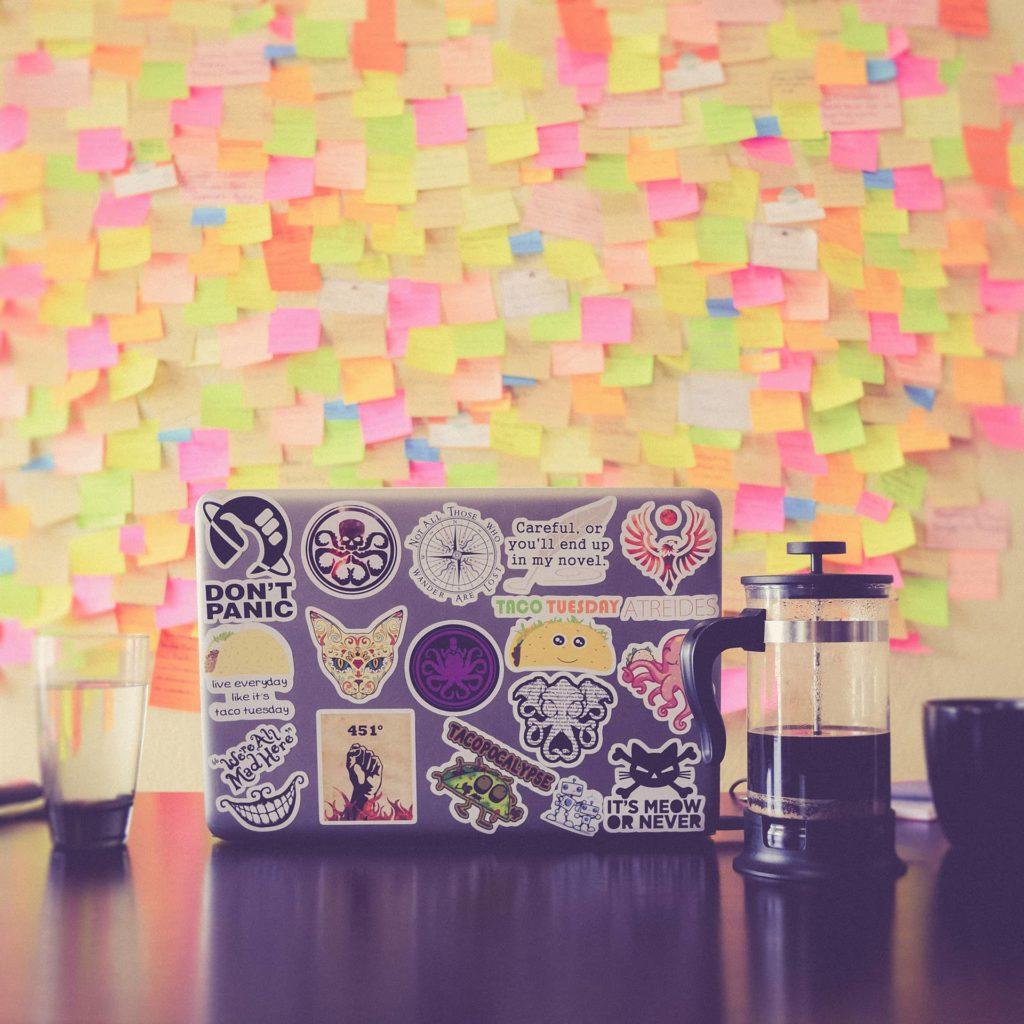 Un ordinateur portable, rempli de stickers, devant un mur de post-it, le bureau parfait d'un UX Designer