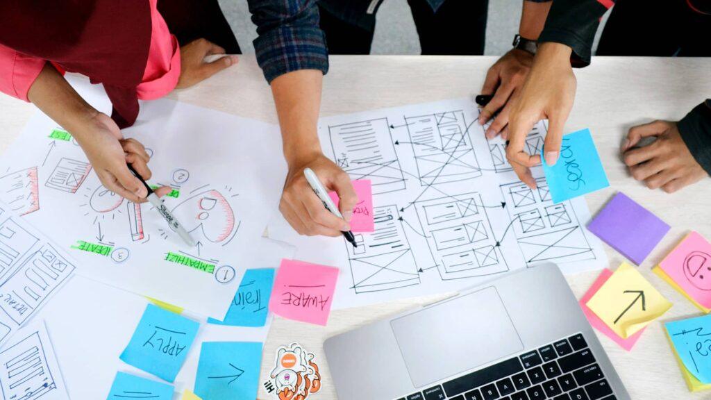 L'UX Design illustré par des wireframes, des post-its et des personnes brainstormant