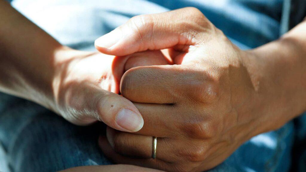 Des mains de soignants et patients se joignant pour s'apporter du courage