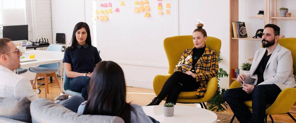 Un groupe de designers discutant d'un projet autour d'une table.